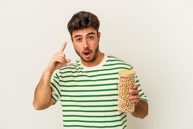 Jeune homme de race blanche tenant un pot de pois chiches isolé sur fond blanc ayant une idée, un concept d'inspiration.