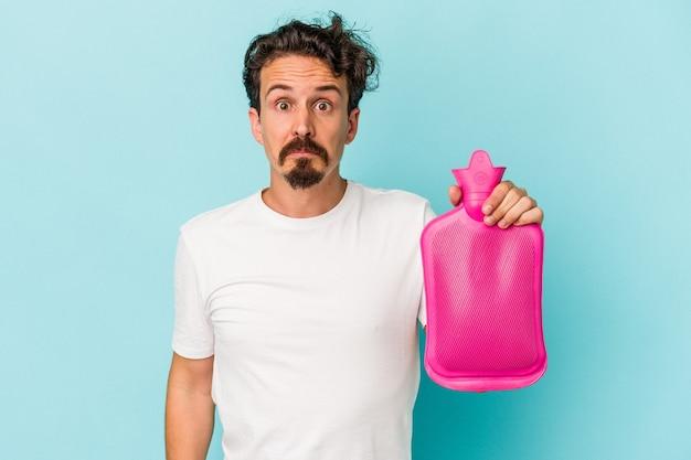 Jeune homme de race blanche tenant un sac d'eau isolé sur fond bleu hausse les épaules et ouvre les yeux confus.