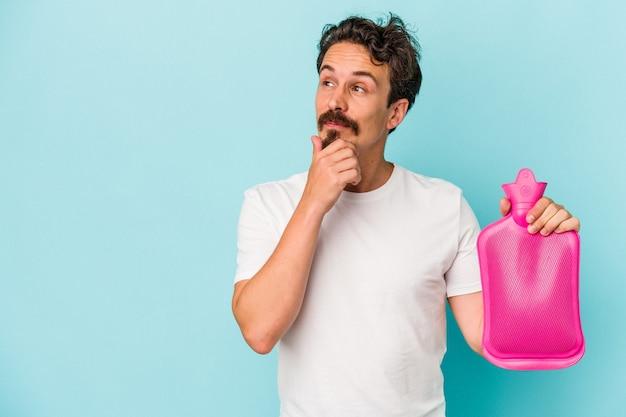 Jeune homme de race blanche tenant un sac d'eau isolé sur fond bleu regardant de côté avec une expression douteuse et sceptique.