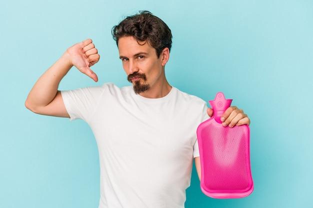 Jeune homme de race blanche tenant un sac d'eau isolé sur fond bleu se sent fier et confiant, exemple à suivre.