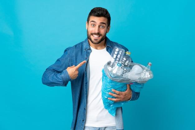 Jeune homme de race blanche tenant un sac plein de bouteilles en plastique à recycler isolé sur un mur bleu avec une expression faciale surprise