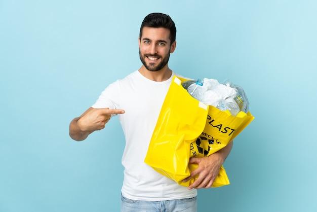 Jeune homme de race blanche tenant un sac plein de bouteilles en plastique à recycler isolé sur mur bleu et en le pointant