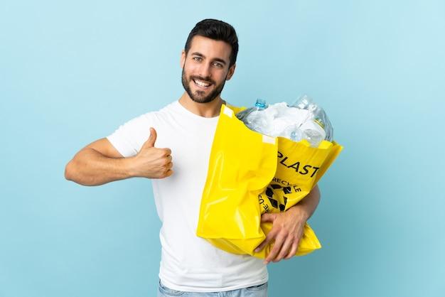 Jeune homme de race blanche tenant un sac plein de bouteilles en plastique à recycler isolé sur mur bleu avec les pouces vers le haut parce que quelque chose de bien s'est passé