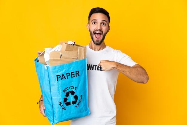 Jeune homme de race blanche tenant un sac de recyclage plein de papier à recycler isolé sur fond blanc avec une expression faciale surprise