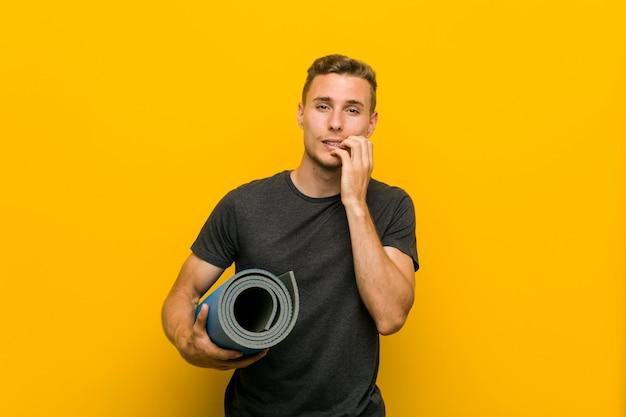 Jeune homme de race blanche tenant un tapis se ronger les ongles, nerveux et très inquiet.