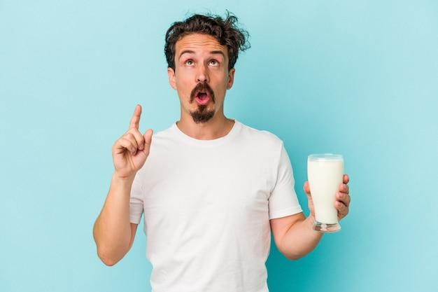 Jeune homme de race blanche tenant un verre de lait isolé sur fond bleu pointant vers le haut avec la bouche ouverte.