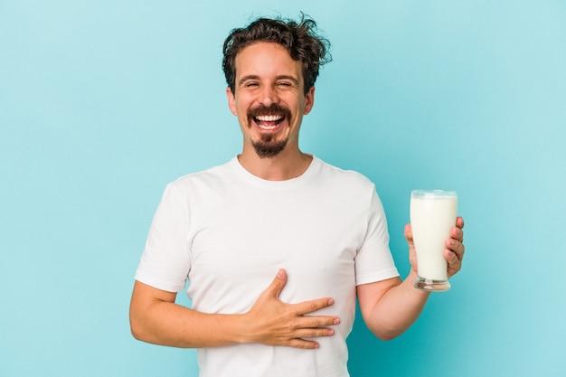 Jeune homme de race blanche tenant un verre de lait isolé sur fond bleu en riant et en s'amusant.