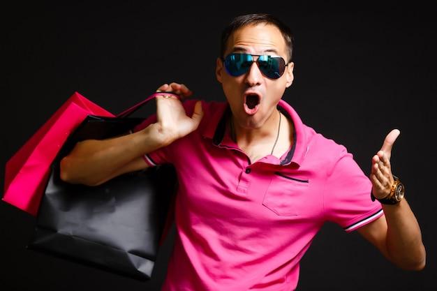 Jeune homme de race blanche tient des sacs à provisions