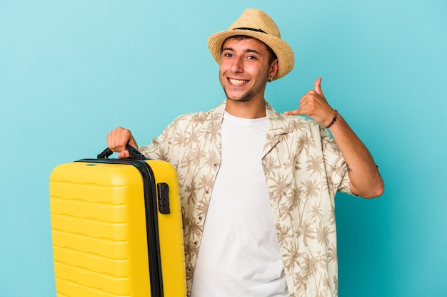 Jeune homme de race blanche va voyager isolé sur fond bleu montrant un geste d'appel de téléphone portable avec les doigts.