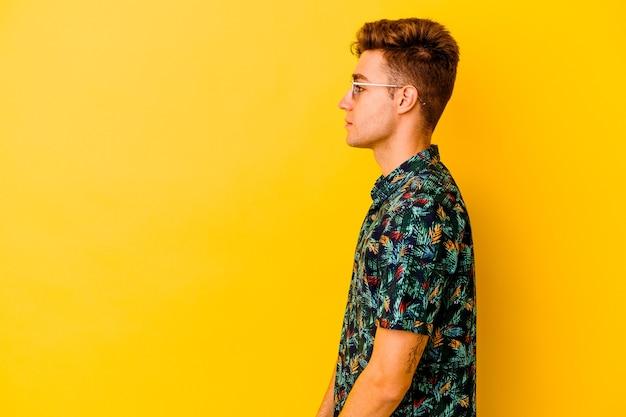 Jeune homme de race blanche vêtu d'une chemise hawaïenne isolée sur un mur jaune regardant à gauche, pose sur le côté.