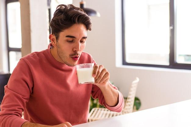 Jeune homme de race mixte buvant du lait pour le petit déjeuner