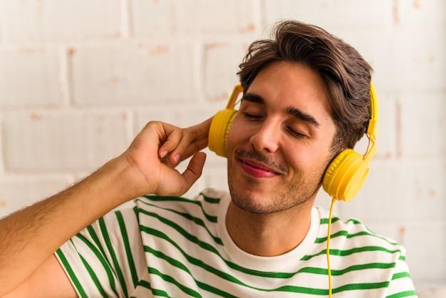 Jeune homme de race mixte écoutant de la musique assis sur le canapé
