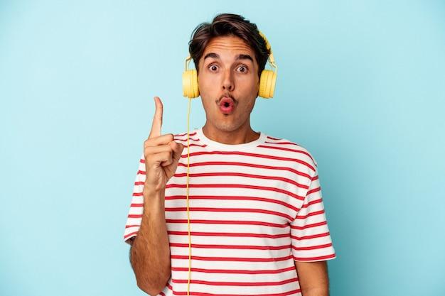 Jeune homme de race mixte écoutant de la musique isolée sur fond bleu ayant une bonne idée, concept de créativité.