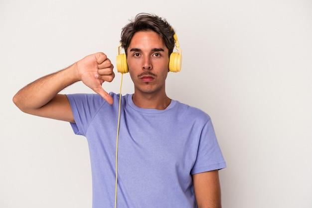 Jeune homme de race mixte écoutant de la musique isolée sur fond bleu montrant un geste d'aversion, les pouces vers le bas. notion de désaccord.