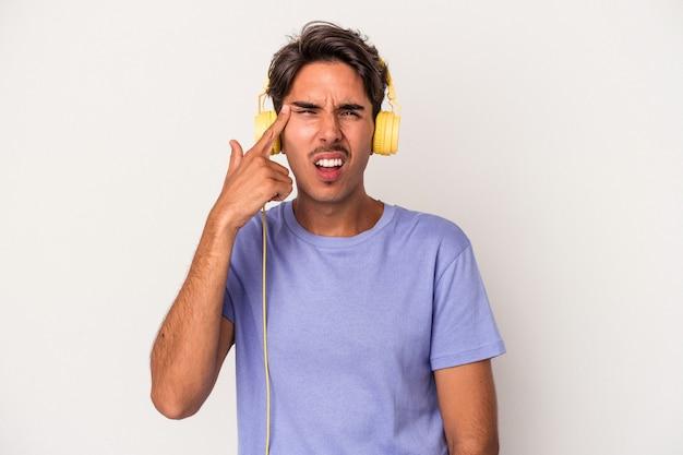 Jeune homme de race mixte écoutant de la musique isolée sur fond bleu montrant un geste de déception avec l'index.