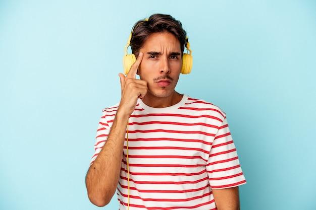 Jeune homme de race mixte écoutant de la musique isolée sur fond bleu pointant le temple avec le doigt, pensant, concentré sur une tâche.