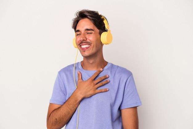 Jeune homme de race mixte écoutant de la musique isolée sur fond bleu rit fort en gardant la main sur la poitrine.