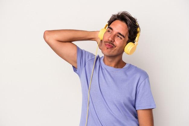 Jeune homme de race mixte écoutant de la musique isolée sur fond bleu touchant l'arrière de la tête, pensant et faisant un choix.