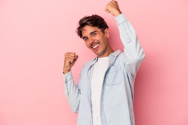 Jeune homme de race mixte isolé sur fond blanc acclamant insouciant et excité. notion de victoire.