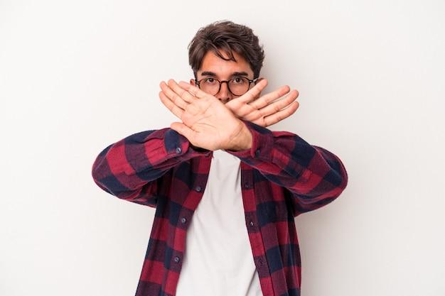 Jeune homme de race mixte isolé sur fond blanc faisant un geste de déni