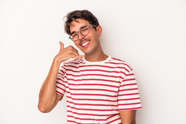 Jeune homme de race mixte isolé sur fond blanc montrant un geste d'appel de téléphone portable avec les doigts.