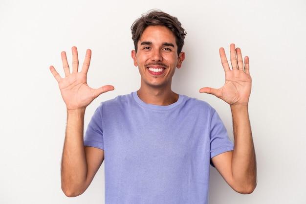 Jeune homme de race mixte isolé sur fond blanc montrant le numéro dix avec les mains.