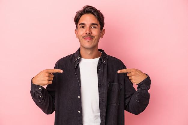 Jeune homme de race mixte isolé sur fond blanc personne pointant à la main vers un espace de copie de chemise, fier et confiant