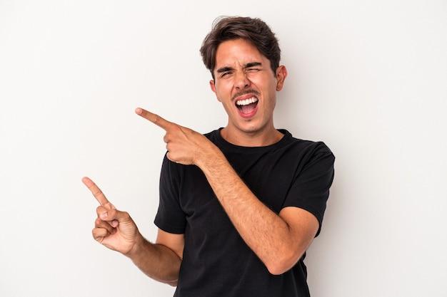 Jeune homme de race mixte isolé sur fond blanc pointant avec les index vers un espace de copie, exprimant l'excitation et le désir.