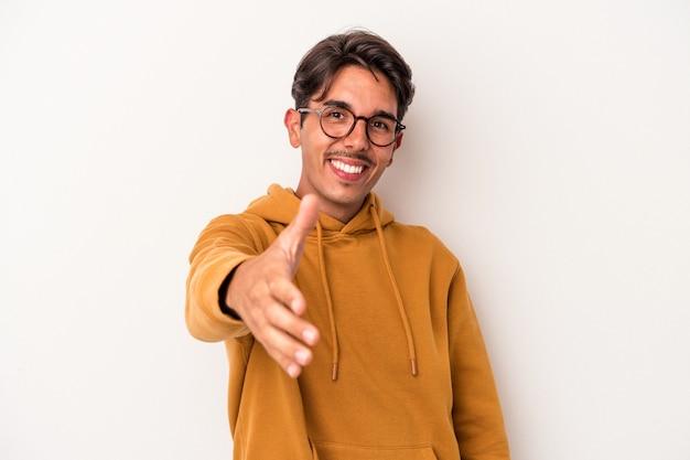 Jeune homme de race mixte isolé sur fond blanc s'étendant la main à la caméra en geste de salutation.