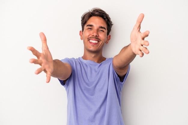 Jeune homme de race mixte isolé sur fond blanc se sent confiant en donnant un câlin à la caméra.