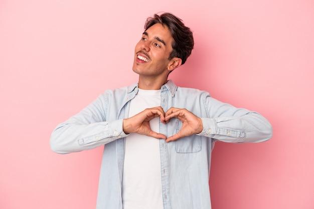 Jeune homme de race mixte isolé sur fond blanc souriant et montrant une forme de coeur avec les mains.