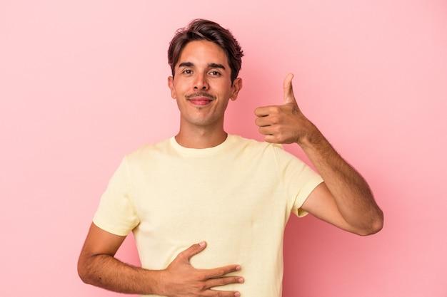 Un jeune homme de race mixte isolé sur fond blanc touche le ventre, sourit doucement, mange et satisfait le concept.