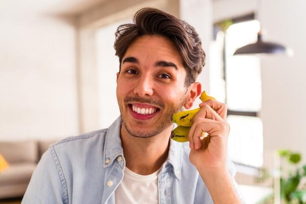 Jeune homme de race mixte mangeant une banane dans une cuisine de sa maison