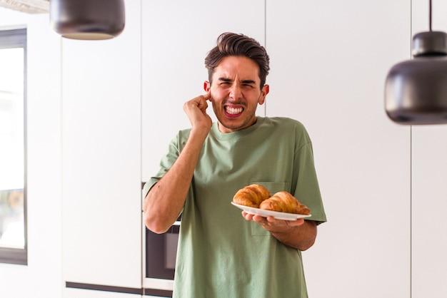 Jeune homme de race mixte mangeant un croissant dans une cuisine le matin couvrant les oreilles avec les mains.