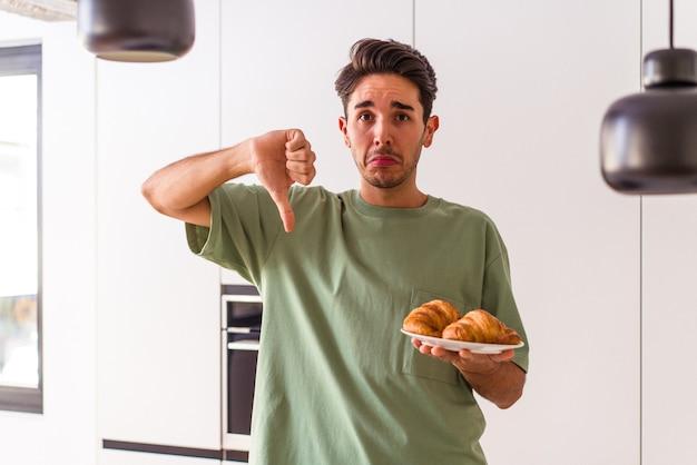 Jeune homme de race mixte mangeant un croissant dans une cuisine le matin montrant un geste d'aversion, les pouces vers le bas. notion de désaccord.