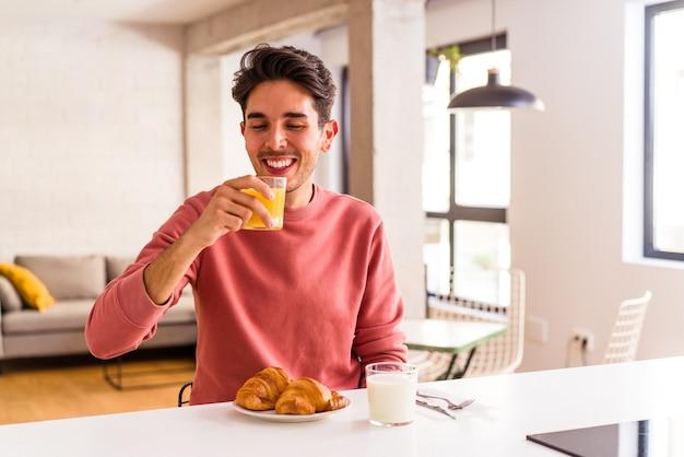 Jeune homme de race mixte mangeant un croissant dans une cuisine le matin