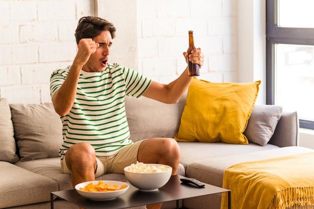 Jeune Homme De Race Mixte Mangeant Du Pop-corn Assis Sur Le Canapé Photo Premium