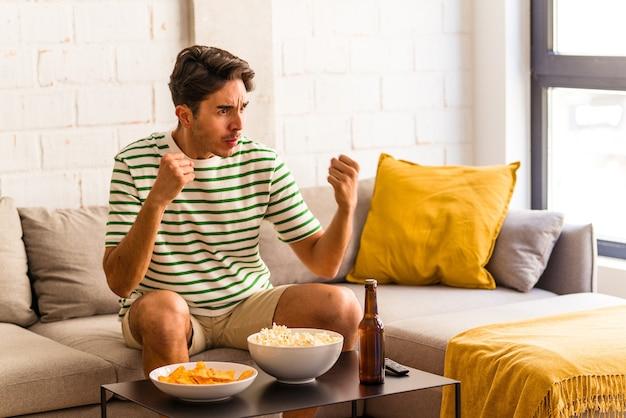 Jeune homme de race mixte mangeant du pop-corn assis sur le canapé