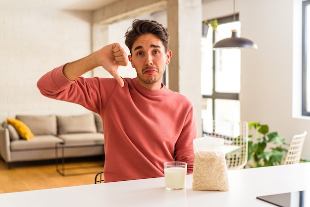 Jeune homme de race mixte mangeant des flocons d'avoine et du lait pour le petit-déjeuner dans sa cuisine montrant un geste d'aversion, les pouces vers le bas. notion de désaccord.