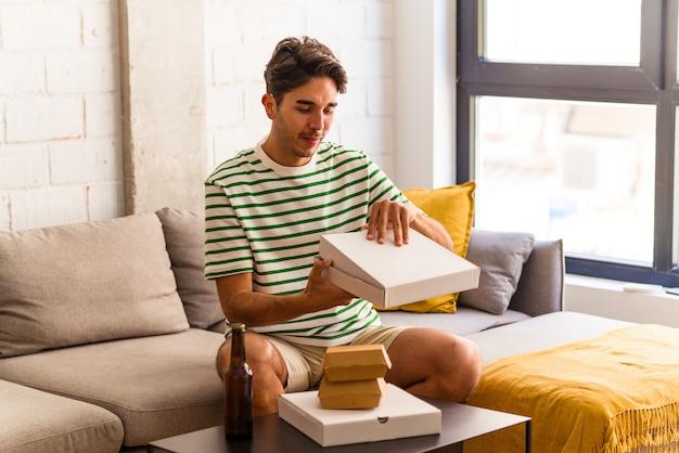 Jeune homme de race mixte mangeant des pizzas et des hamburgers et buvant des bières