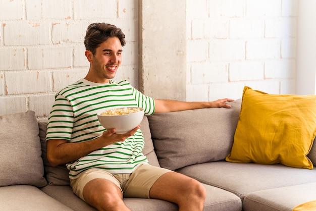 Jeune homme de race mixte mangeant des pop-corn assis sur le canapé