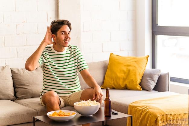 Jeune homme de race mixte mangeant des pop-corns assis sur le canapé essayant d'écouter des potins.