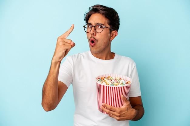 Jeune homme de race mixte mangeant des pop-corns isolés sur fond bleu ayant une idée, un concept d'inspiration.