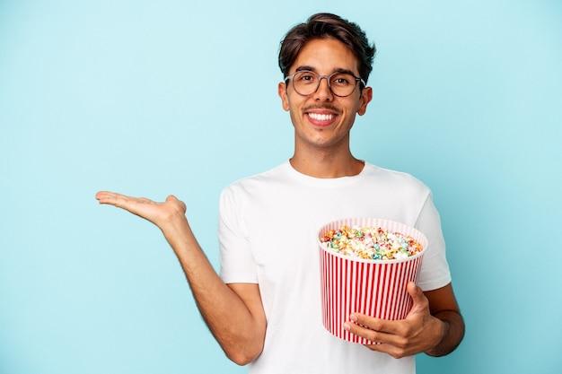 Jeune homme de race mixte mangeant des pop-corns isolés sur fond bleu montrant un espace de copie sur une paume et tenant une autre main sur la taille.