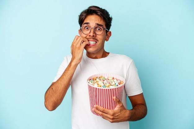 Jeune homme de race mixte mangeant des pop-corns isolés sur fond bleu se rongeant les ongles, nerveux et très anxieux.