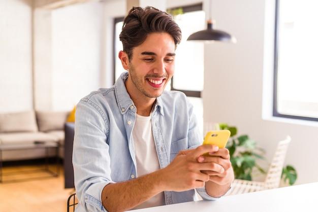 Jeune homme de race mixte parlant au téléphone dans une cuisine