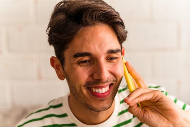 Jeune homme de race mixte parlant au téléphone sur son canapé