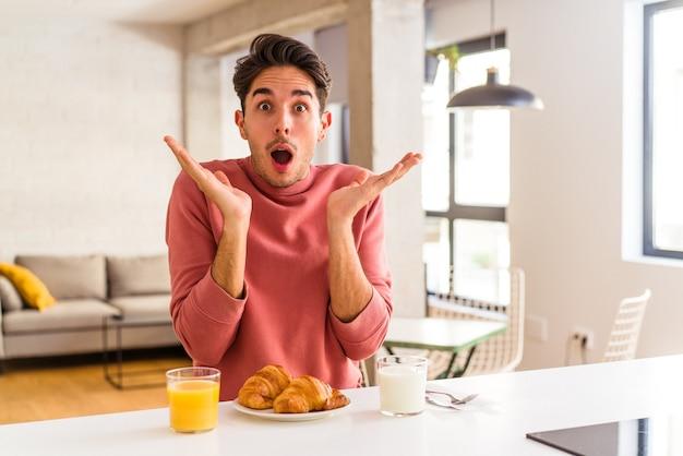 Jeune homme de race mixte prenant son petit déjeuner dans une cuisine le matin surpris et choqué.