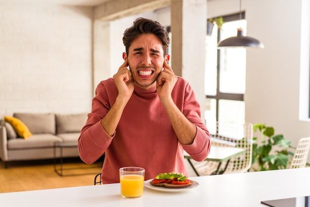 Jeune homme de race mixte prenant son petit déjeuner dans sa cuisine couvrant les oreilles avec les mains.