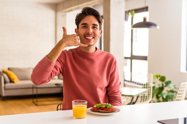 Jeune homme de race mixte prenant son petit déjeuner dans sa cuisine montrant un geste d'appel de téléphone portable avec les doigts.